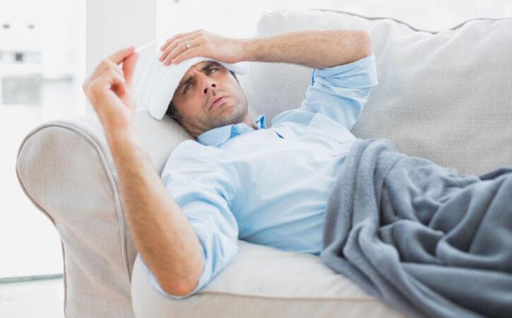мужчина меряет температуру при гриппе